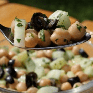 Chickpea cucumber salad on spoon with bowl in background