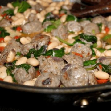 Italian sausage and white beans cooking in a skillet