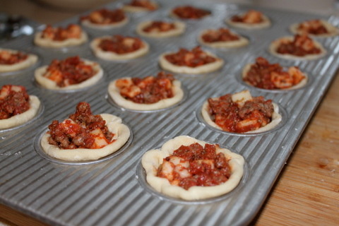 Mini muffin tins filled with stuffed pizza pie bites ready for the oven.