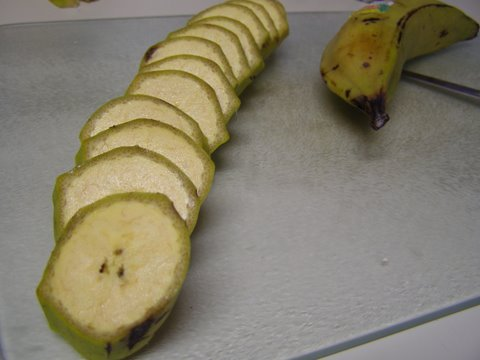 Sliced plantain on a cutting board with peel still on