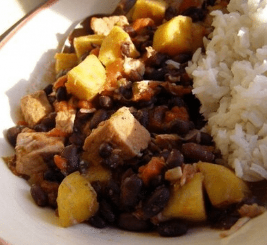 A serving of Caribbean Pork Stew with a scoop of rice in a bowl.