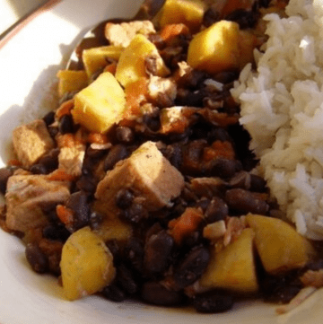 Serving of caribbean pork stew in a bowl with a spoonful of white rice.