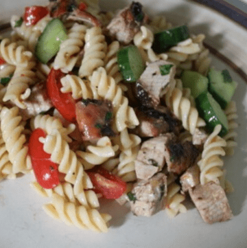 A serving of turkey & pesto pasta salad on a cream colored dinner plate.