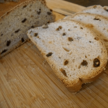 Slices of homemade cinnamon raisin bread on a cutting board.