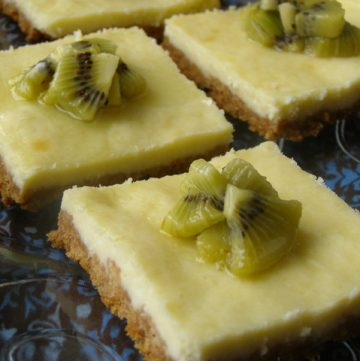 Slices of cut kiwi-glazed cheesecake bars on a serving platter.