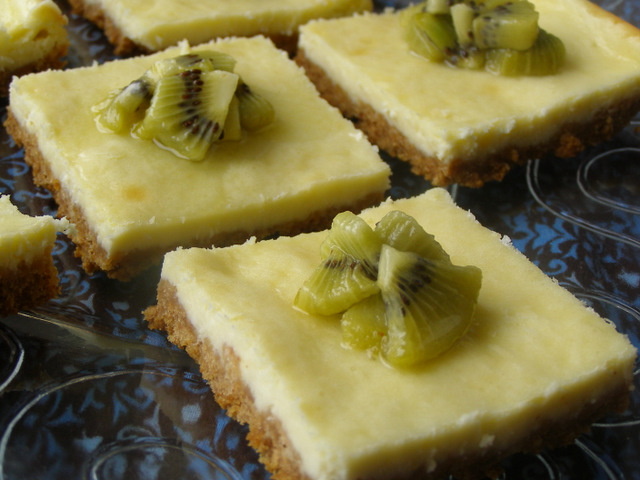 Slice of Kiwi-Glazed Cheesecake Bars on a glass serving platter.