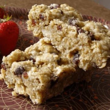 Two individual oatmeal breakfast bars stacked on a plate with strawberries on the side.