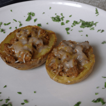 Two taco stuffed potato skins on a plate