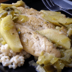 a serving of chicken with leeks and apples over barley on a black plate