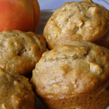 four peach muffins on a plate with a fresh peach